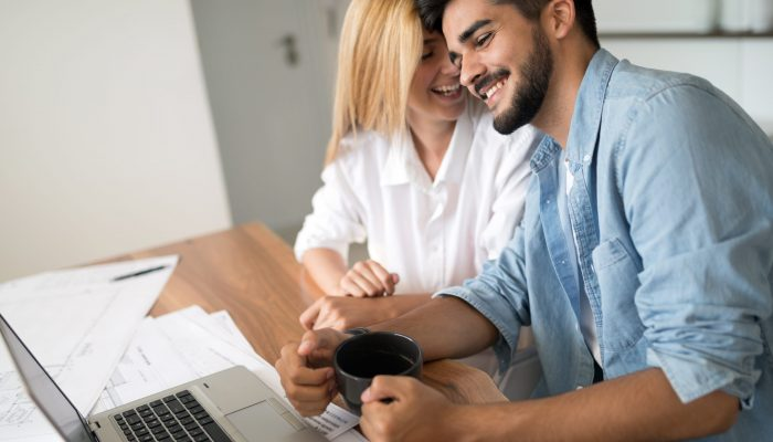Photo of cheerful loving young couple using laptop and analyzing their finances with documents