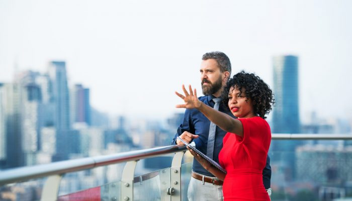 A portrait of businesspeople standing against London rooftop view, leaning on a railing and talking.